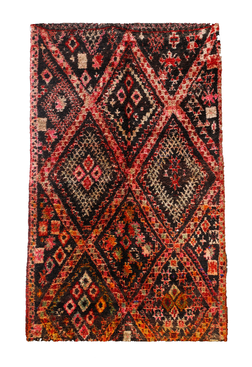BENI M'GUILD CARPETS   These carpets are made in the western Middle Atlas of Morocco with very thick in pile and simple geometric designs against bright, bold backgrounds of red, blue, green, and black.