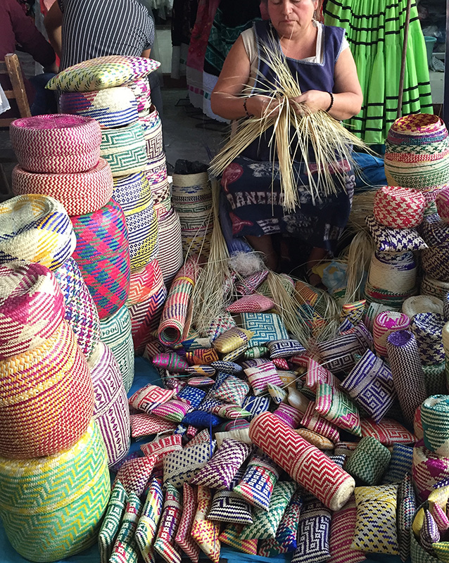 Woman weaving palm baskets at the market