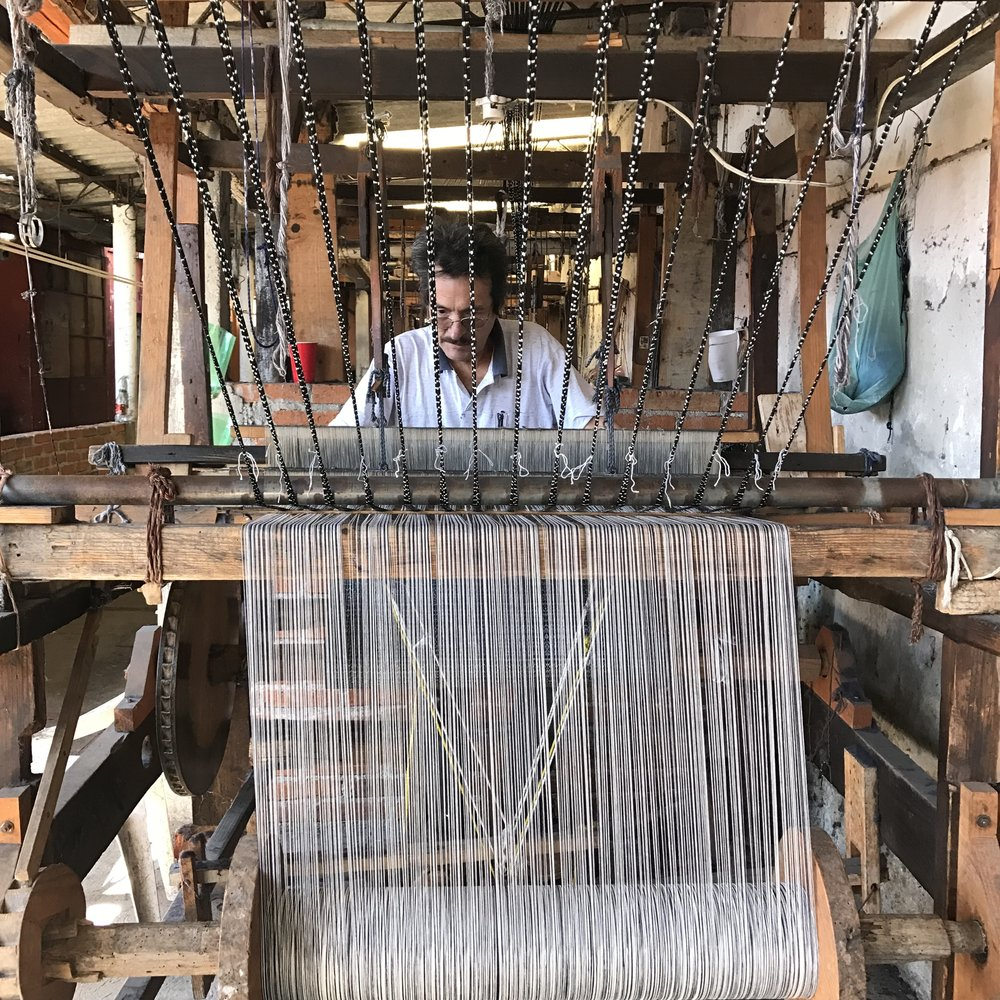 Artisan weaving the loom