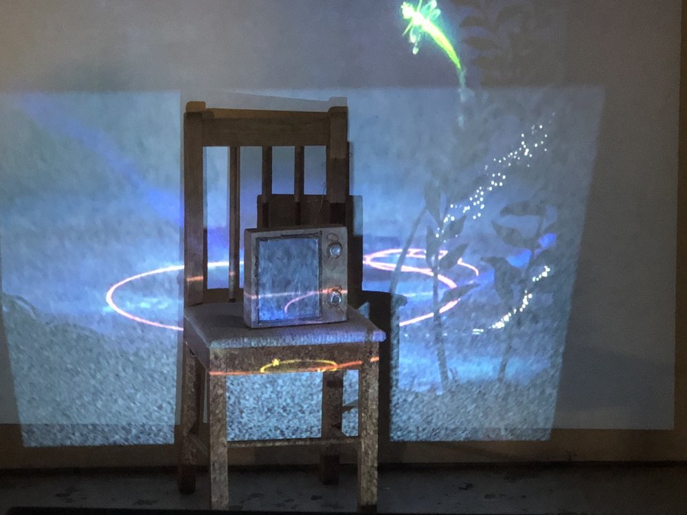 "Student: Hanna Kesty Class: Sculpture I Project: ""Threes"" Cast aluminum, cedar, projected video, found chair. 2018"