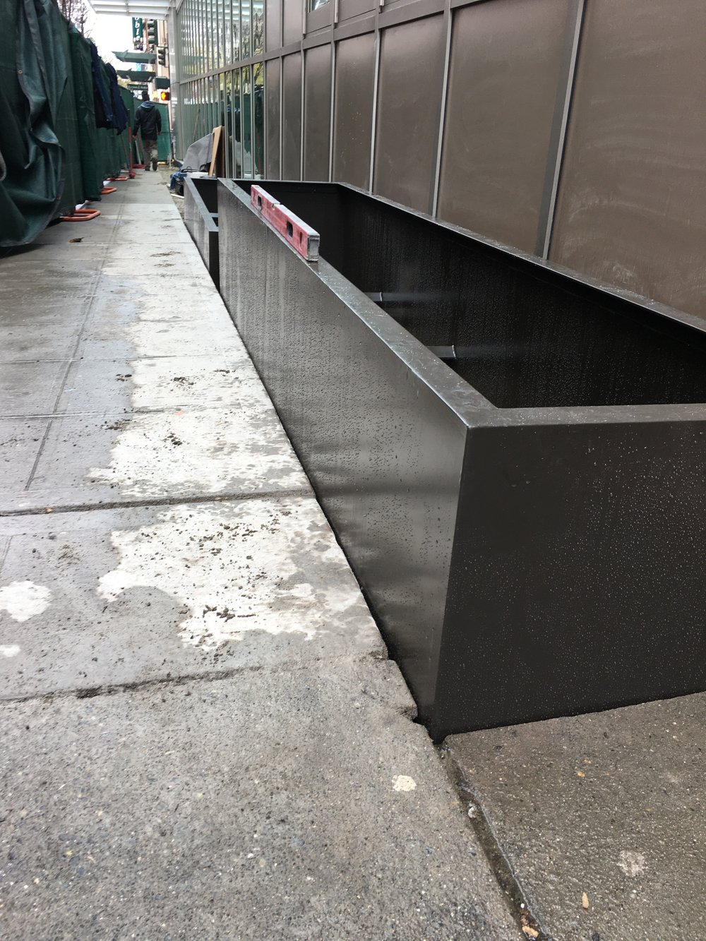 Installing streetscape planters with adjustable leveling feet.
