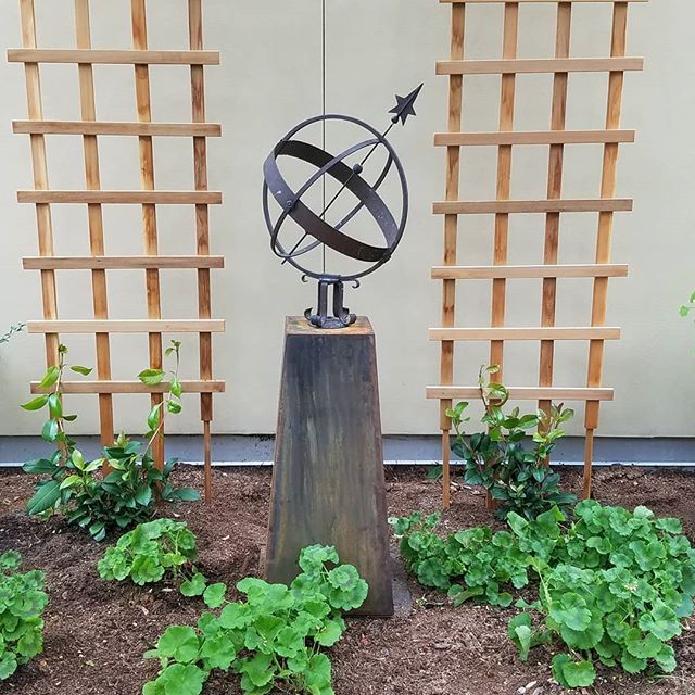 Our taper planter also works great as a pedestal/base.  The client wanted to showcase her family's antique armillary using our planter.  #landscapedesign #landscape planter #patina #seattle