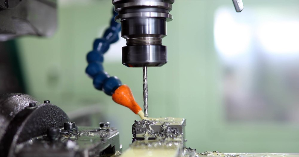 Drilling a hole into a metal part during fabrication.