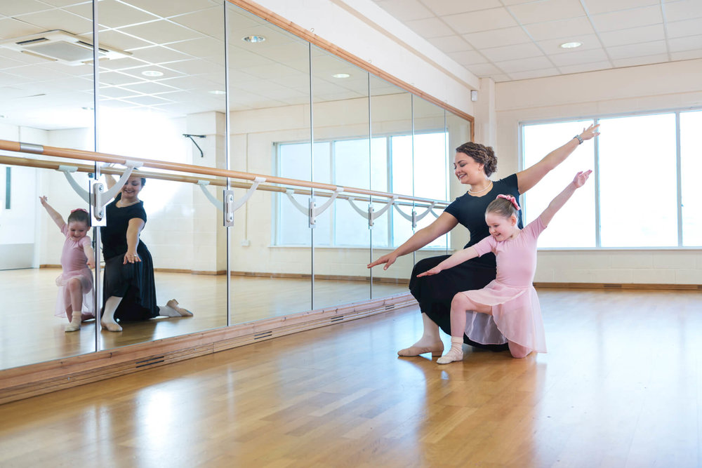rnsd-ballet-school-tiny-dancer-diaganol-arms-at-barre-teacher-smiling.jpg