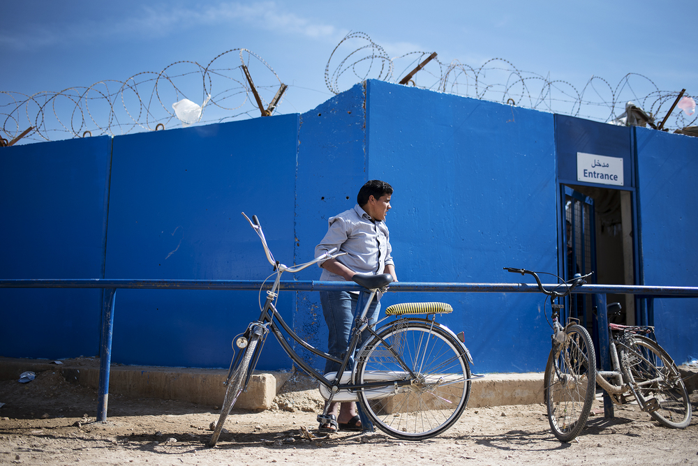 A Syrian refugee unchains his bike at a UNHCR distribution site in Jordan's Zaatari refugee camp, some six miles from Jordan's northern city of Mafraq. February 2016.