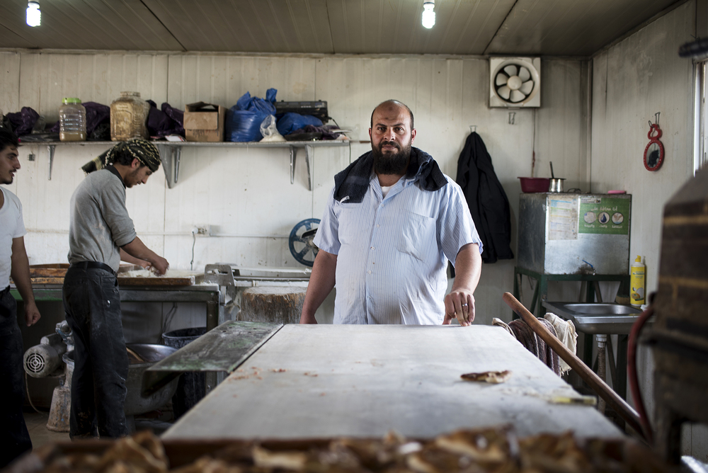 A Syrian refugee pauses at work inside a bakery in Jordan's Zaatari refugee camp, February 2016.