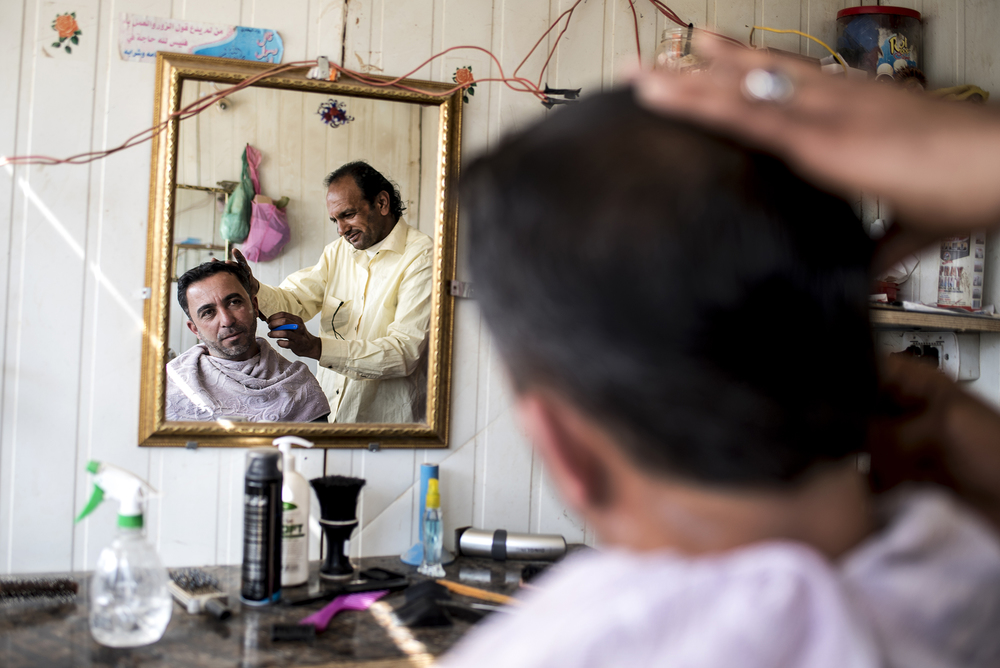 A refugee gets a haircut in Jordan's Zaatari refugee camp. Since its inception in 2012, the camp has swelled to house some 75,000 Syrians. February 2016.