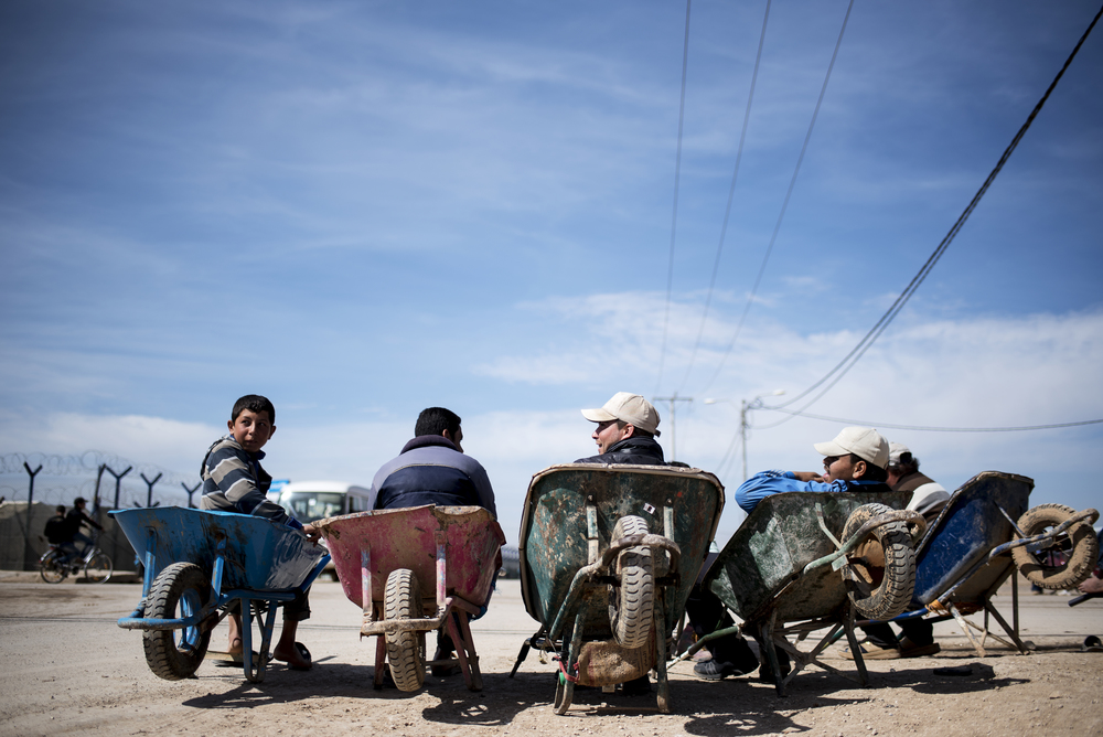 Syrian refugees sit on wheelbarrows at the entrance of Jordan's Zaatari refugee camp. The camp's population has swelled since small numbers of the refugees began fleeing to neighboring Jordan in 2012, with some 75,000 living there in 2015, according to UNHCR figures. February 2016.