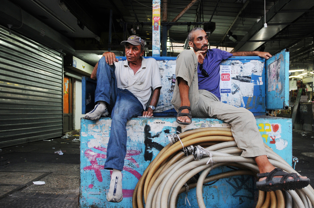 Two merchants rest after Tel Aviv's Shuk Carmel market closes for the day. July 2013.