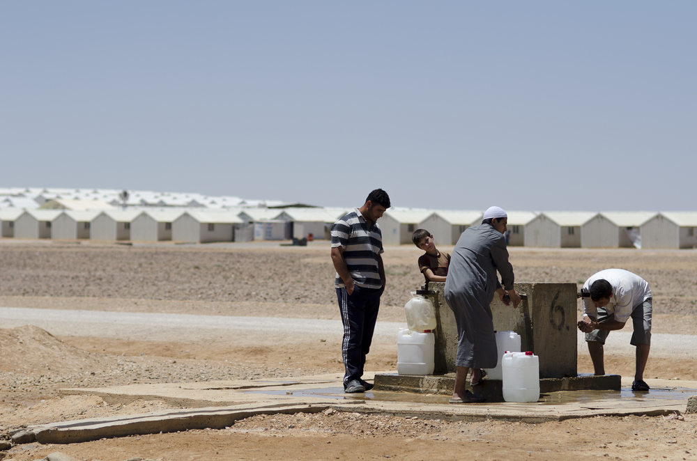 Residents of Jordan's Azraq Refugee Camp for Syrians fill water jugs at one of the camp's pumps. Located in a remote stretch of desert some 50 miles east of the capital Amman, the camp was build in 2014 to eventually house up to 200,000 Syrian refugees.  But over two years since its inception, the camp's population has barely reached 20,000. June 2015.