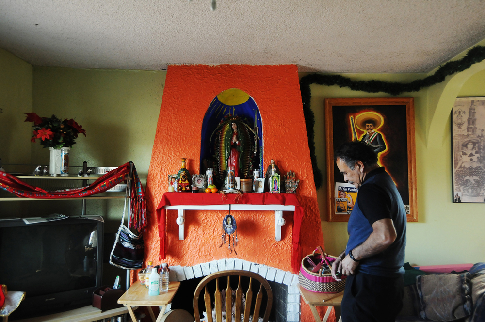 Chacon walks passed an alter in his home used for healing rituals. For patients more comfortable meeting with a curandero, doctors and clinics sometimes call on him to address psychological issues such as anxiety or depression. April 2014.