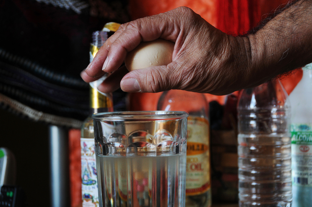 Chacon holds an uncooked egg over water during a cleansing-ritual demonstration. Chacon says the egg represents a single-celled being and is used in several traditional rituals he learned from his grandmother. April 2014.
