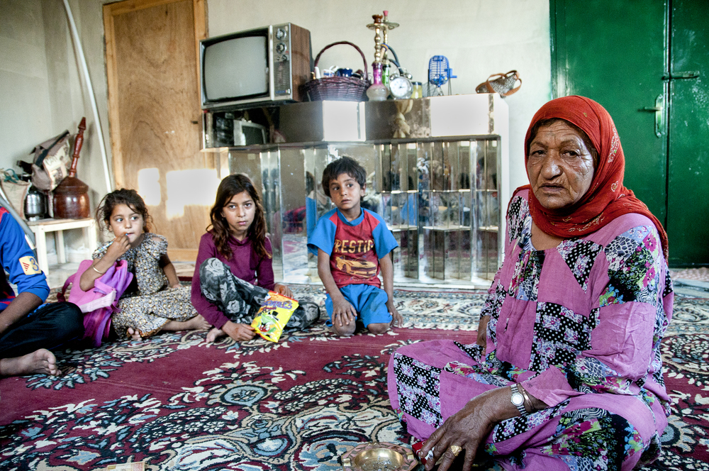Abo Husain's wife sits with their grandchildren in the family's living room in east Amman. July 2013.