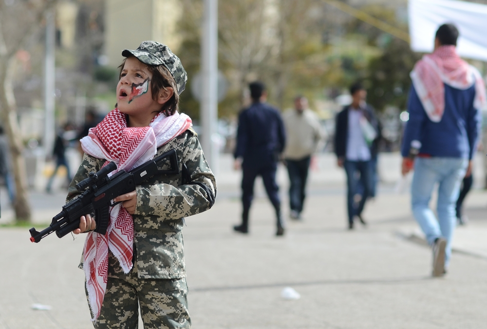 A Jordanian boy holds a toy and dons a traditional Jordanian keffiyeh during a demonstration of solidarity in the capital Amman with Kasasbeh, days the video of his death was released. February 2015.
