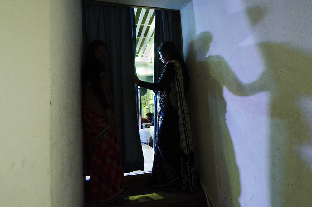 An Indian performer looks on from backstage.