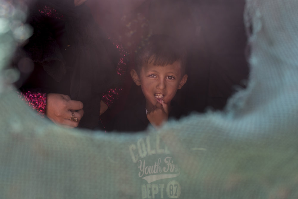 A Syrian child looks out from his family's tent in an informal tent settlement near the northern Jordanian city of Mafraq. July 2015.