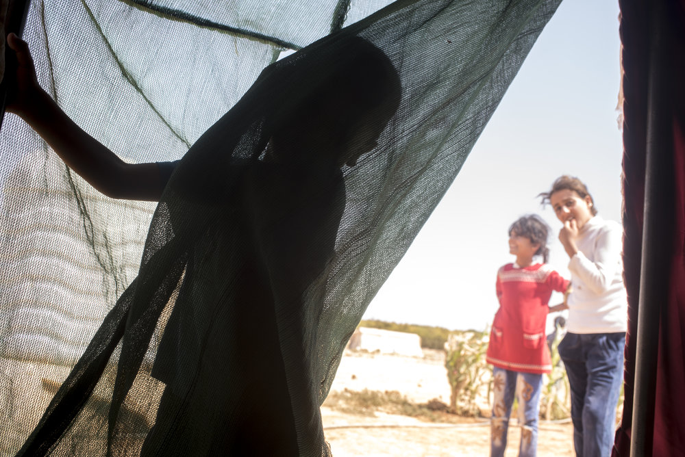Syrian children play inside an informal tent settlement near the northern Jordanian city of Mafraq. July 2015.