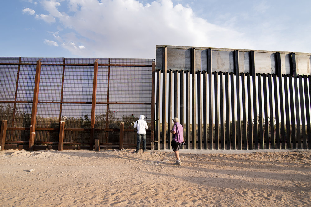Protesters walk along the construction line of a new, bollard-style barrier that broke ground near New Mexico's Santa Teresa Port of Entry along the US-Mexico border in April. June 2018.