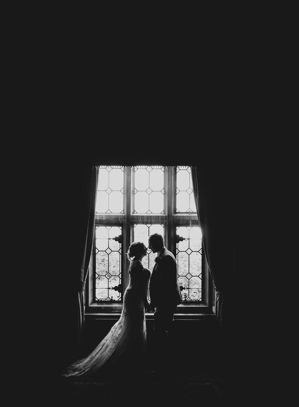 Bride and groom black and white silhouette by a big window at a wedding at Horwood House, Buckinghamshire
