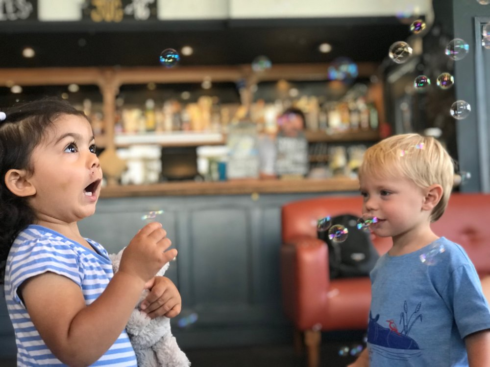 Toddler boy and girl excitedly catching bubbles at Sensory Land class