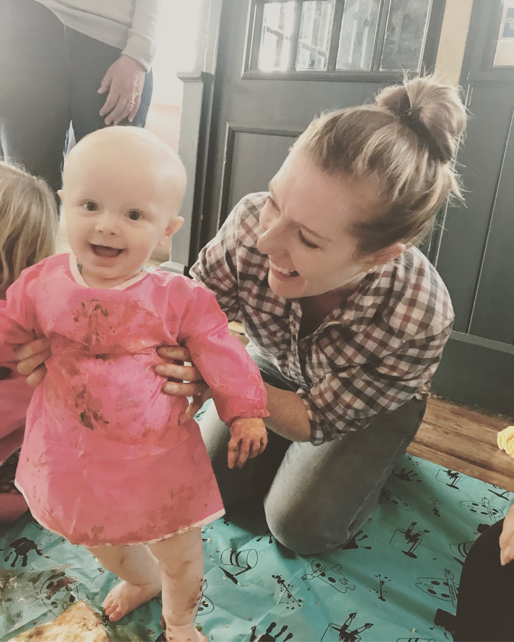Baby wearing pink apron covered in mess being held up by his mother