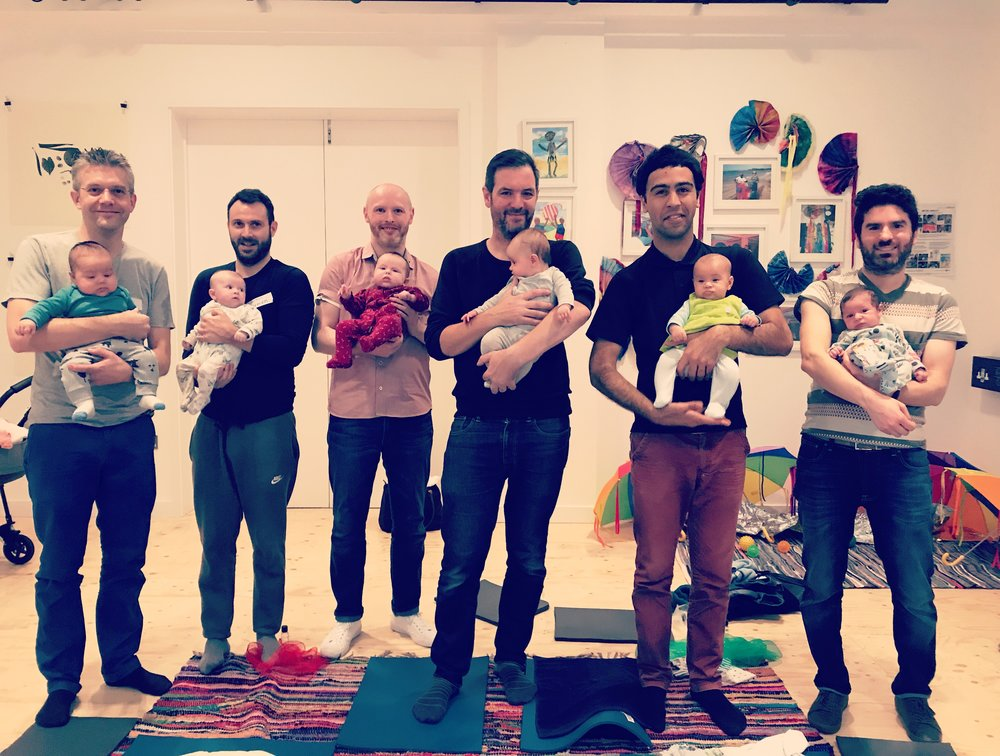Group of 6 fathers standing and holding their babies after doing a baby massage workshop