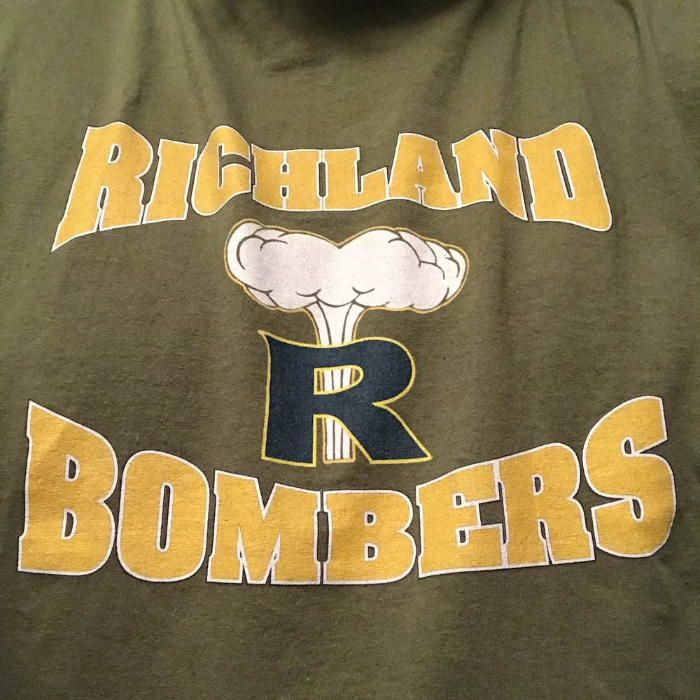 "My alma mater, Richland High School. Originally Columbia High School, its mascot the beaver was changed to the bombers after WWII to commemorate a B-17 bomber called ""The Day's Pay"" which was purchased for the Pacific war effort through a donation of one day's pay by some 51,000 Hanford workers. The flying fortress was commemorated on July 23, 1944. Later, the ""R"" with the mushroom cloud was created for the football team helmets and eventually was adopted as a school symbol. When I was in high school, letterman jackets featured this image on the back with the words ""Nuke 'Em!"" in the cloud."