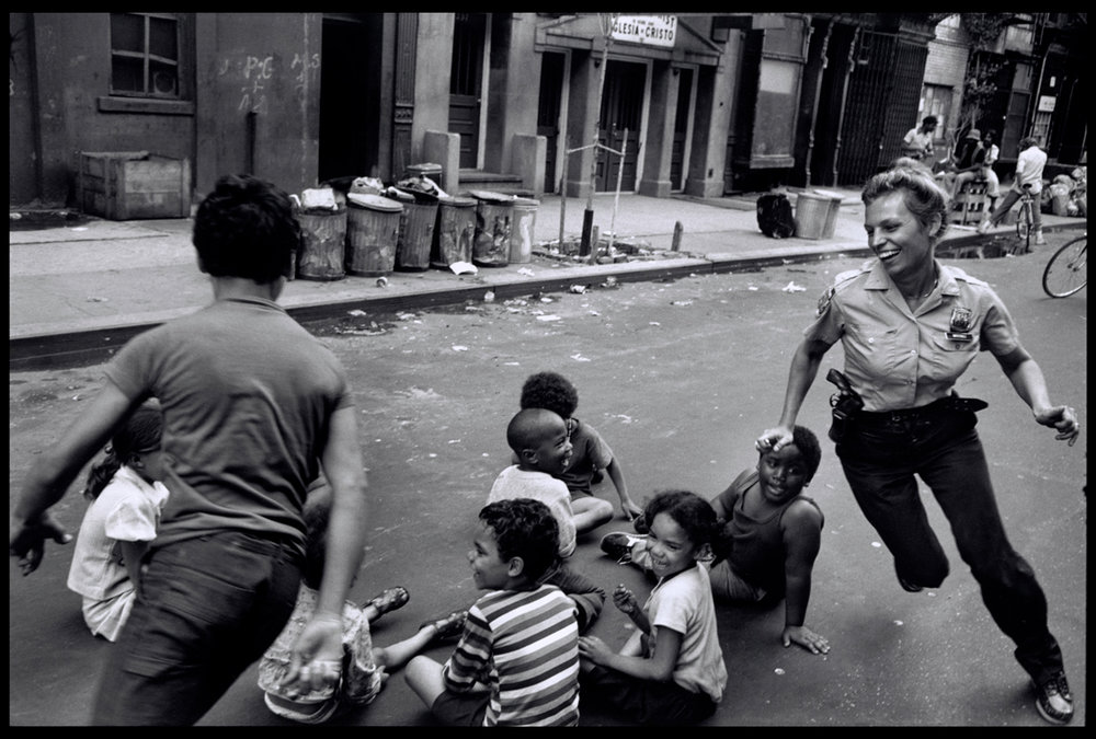 USA, New York City, 1973. A policewoman plays with local kids in Harlem. Credit: Leonard Freed / Magnum Photos / Snapper Media