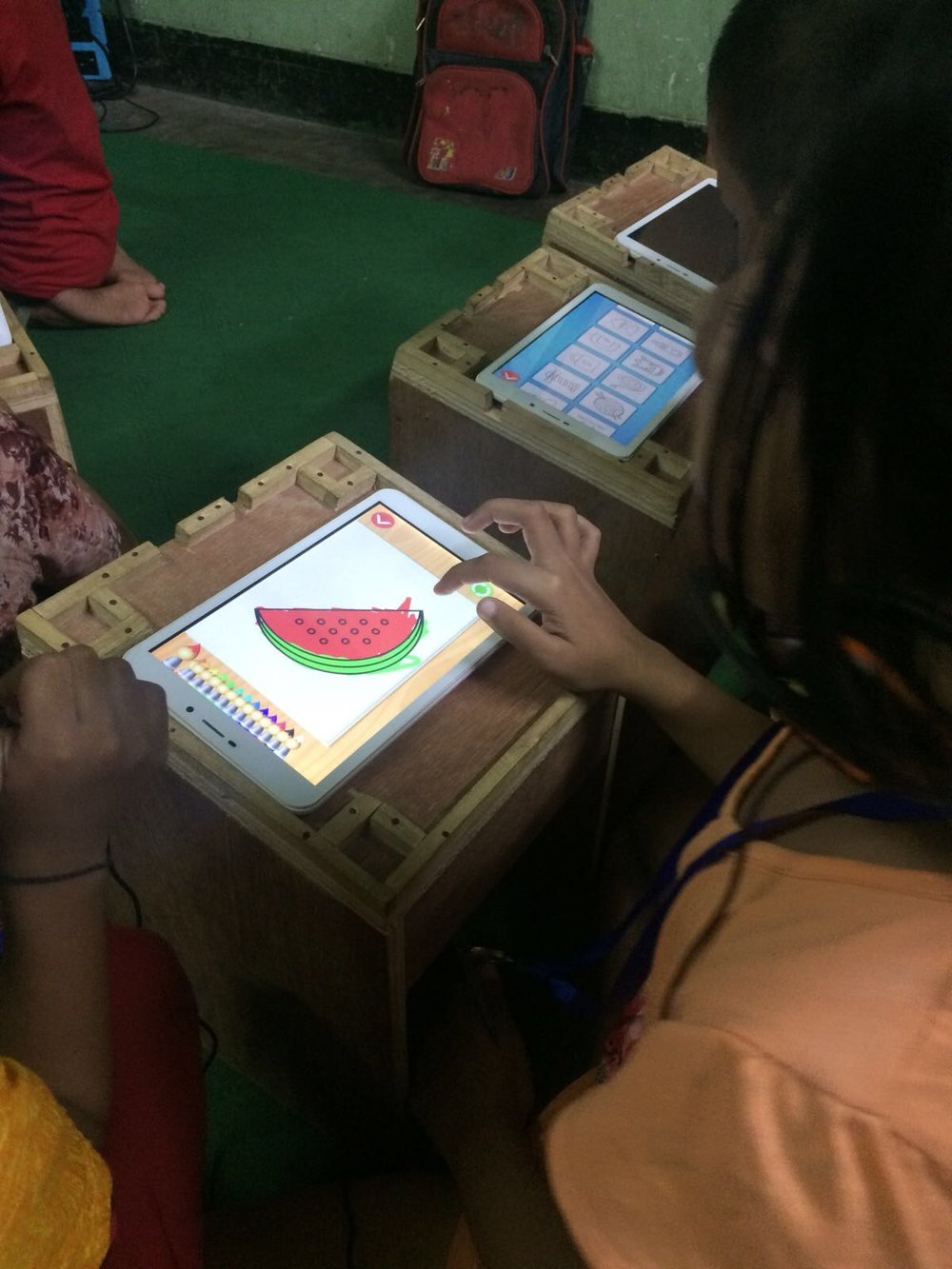 A young girl working with her tablet on a special desk, created by our Teach the World intern, Sunny.