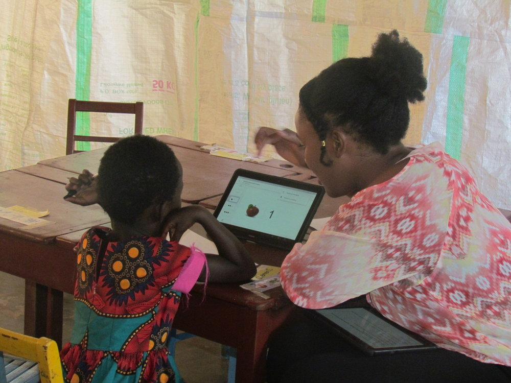 A volunteer conducts the baseline assessment to determine what the children know prior to starting the program
