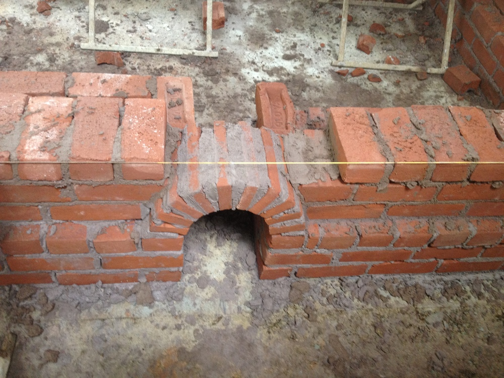 structural masonry, tiny brick arch to allow proper water drainage