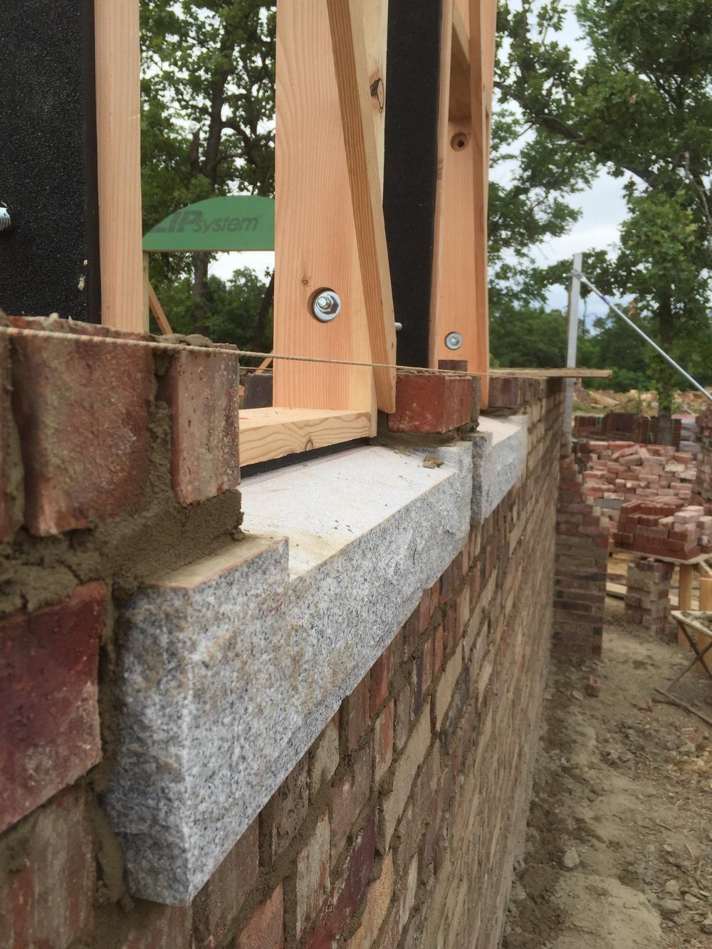 structural masonry, granite window sill with handmade window bucks on top