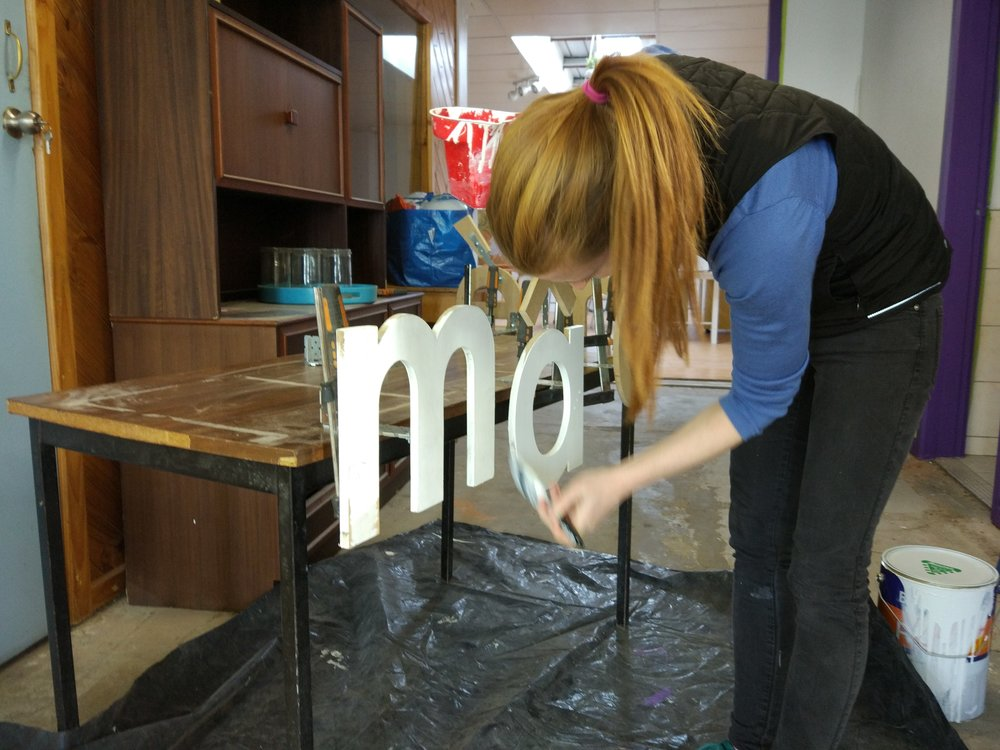 Izzy from fresh sprouts giving the mâché logo a fresh coat
