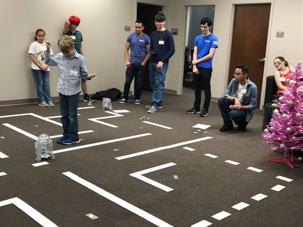 Student counts his team's coins as the droid completes the maze.