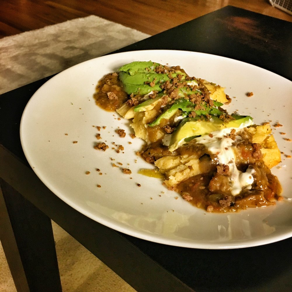 Tamales smothered with pork green chili, sour cream, avocado; topped with pork cracklings.