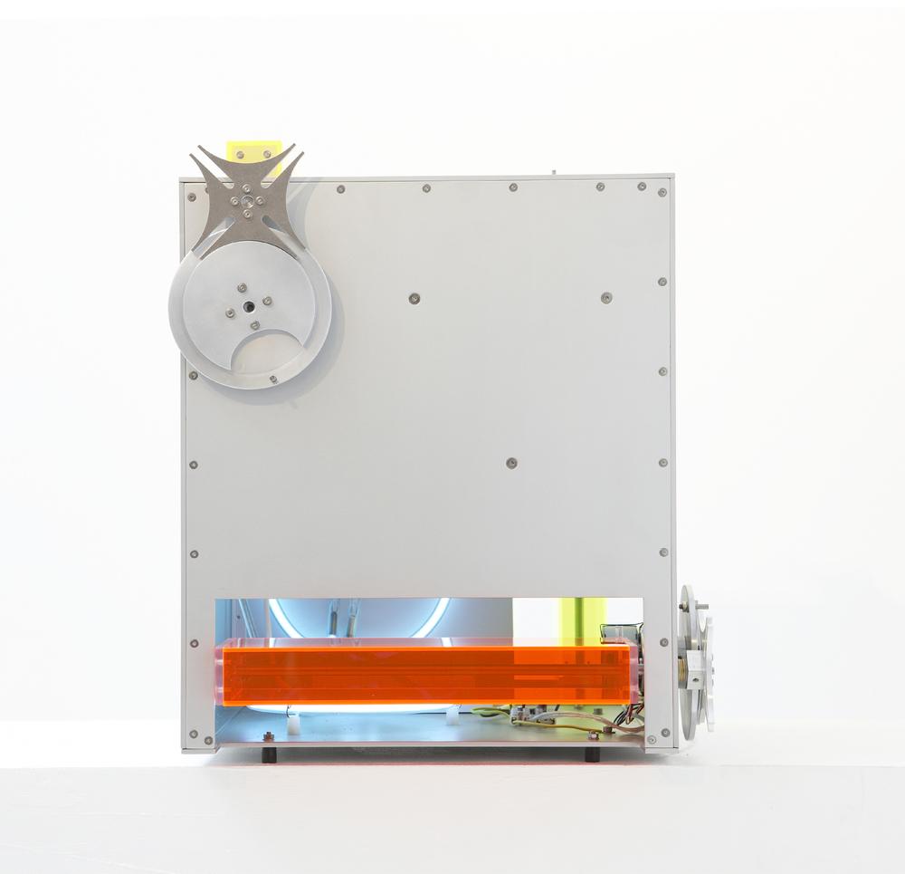 Bodenarbeit III, 2008, ca. 44x44x45 cm, Aluminium, farbiges Plexiglas,Neonsystem Blauentladung, 3 E-Motoren 4 U/min., 3 Malteserkreuzgetriebe
