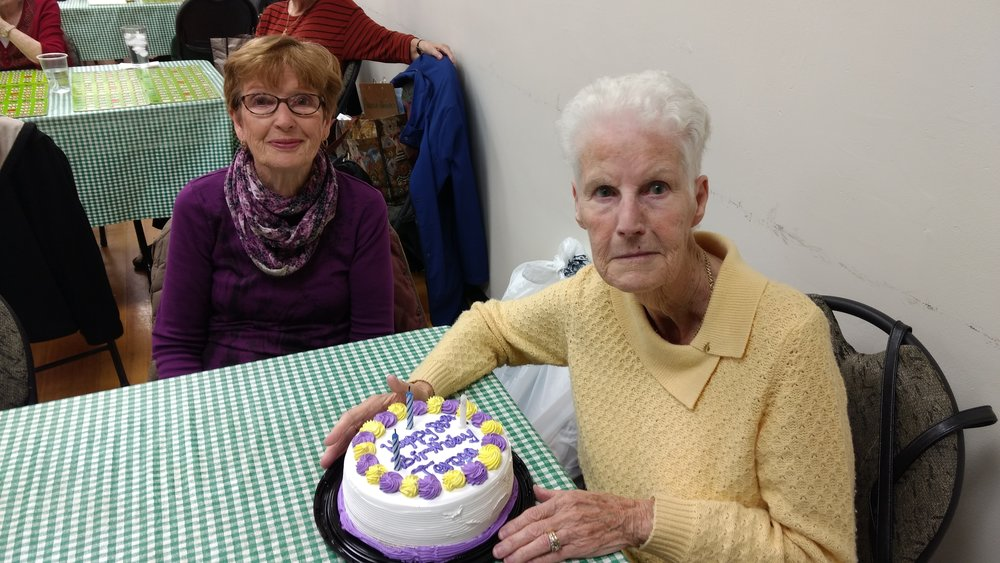 November 2016 - Theresa Gorman enjoying a beautiful cake with Bridget Boggs looking on in anticipation for the cake cutting