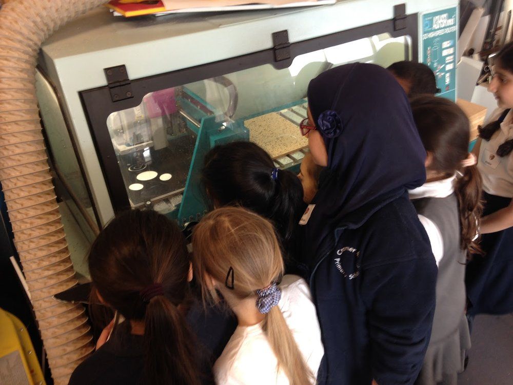 School pupils watching a teddy bear being produced on the CNC router.