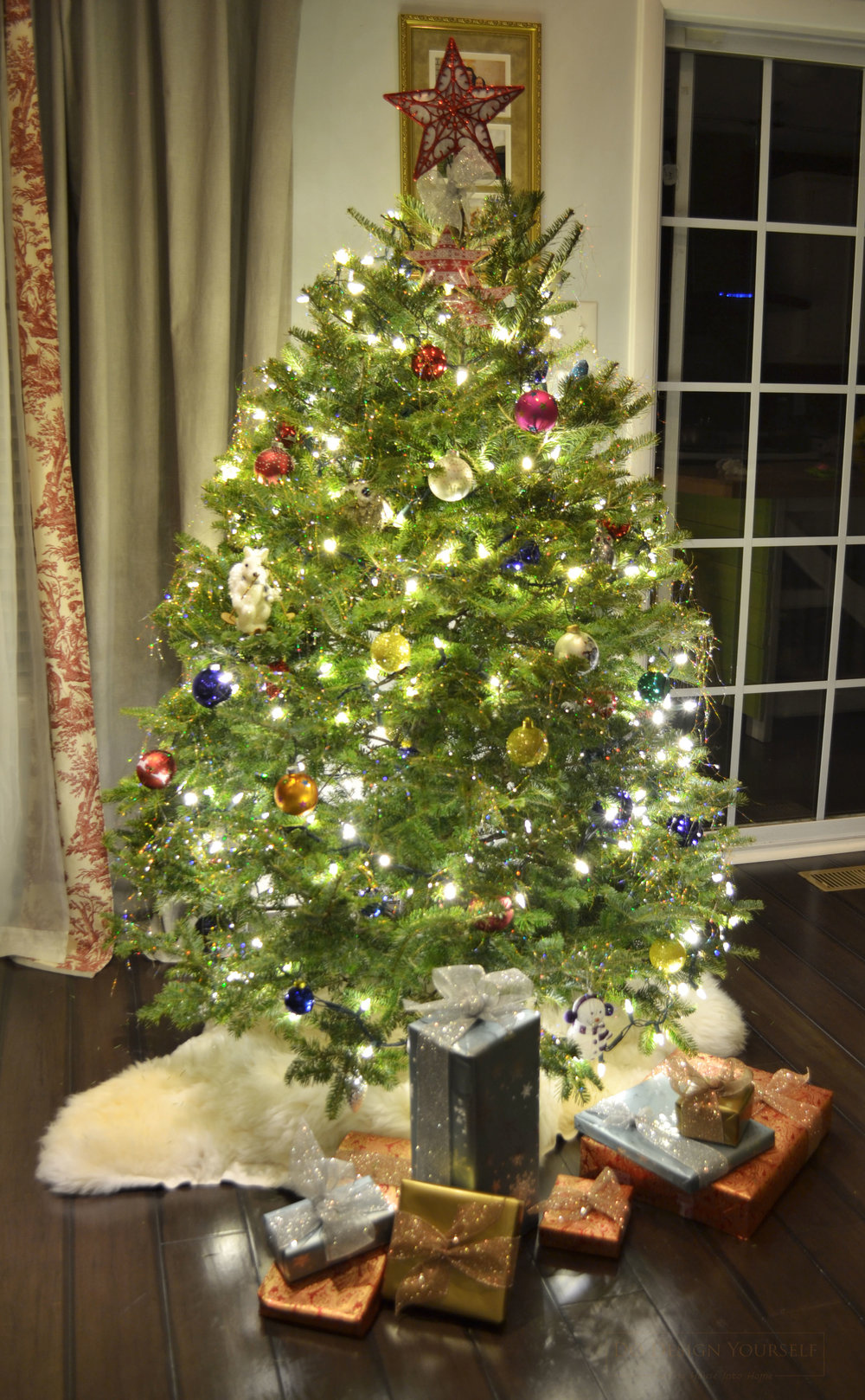 Colorful Christmas tree with white lights, wrapped gift and a white ship skin as a Christmas tree skirt.