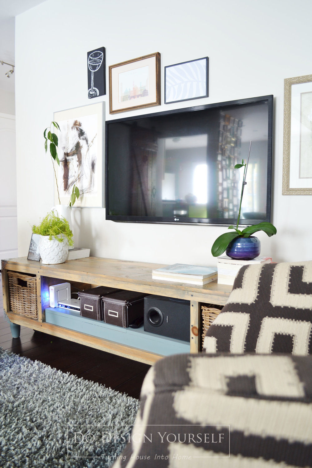 decorate around the TV stand with gallery wall and indoor plants