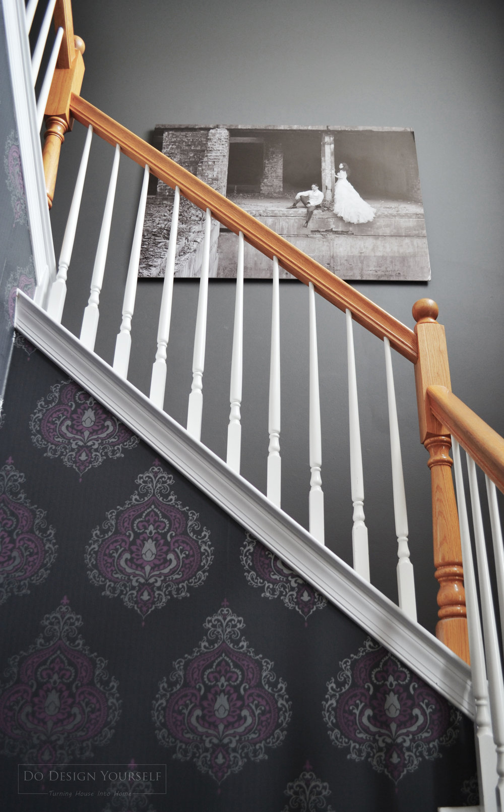 """Gray stair case decorated with the professionally taken enlarged photo from the """"Trash the Dress"""" photosession"""