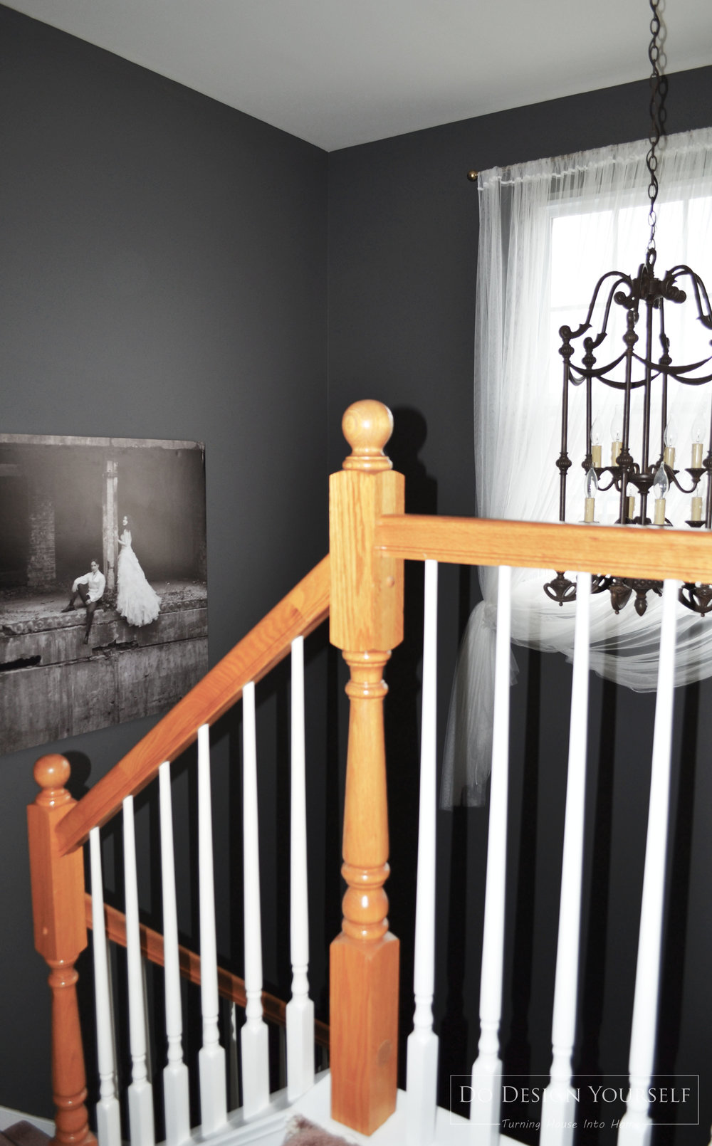 Staircase decorated with over-sized photo art and a shabby chandelier