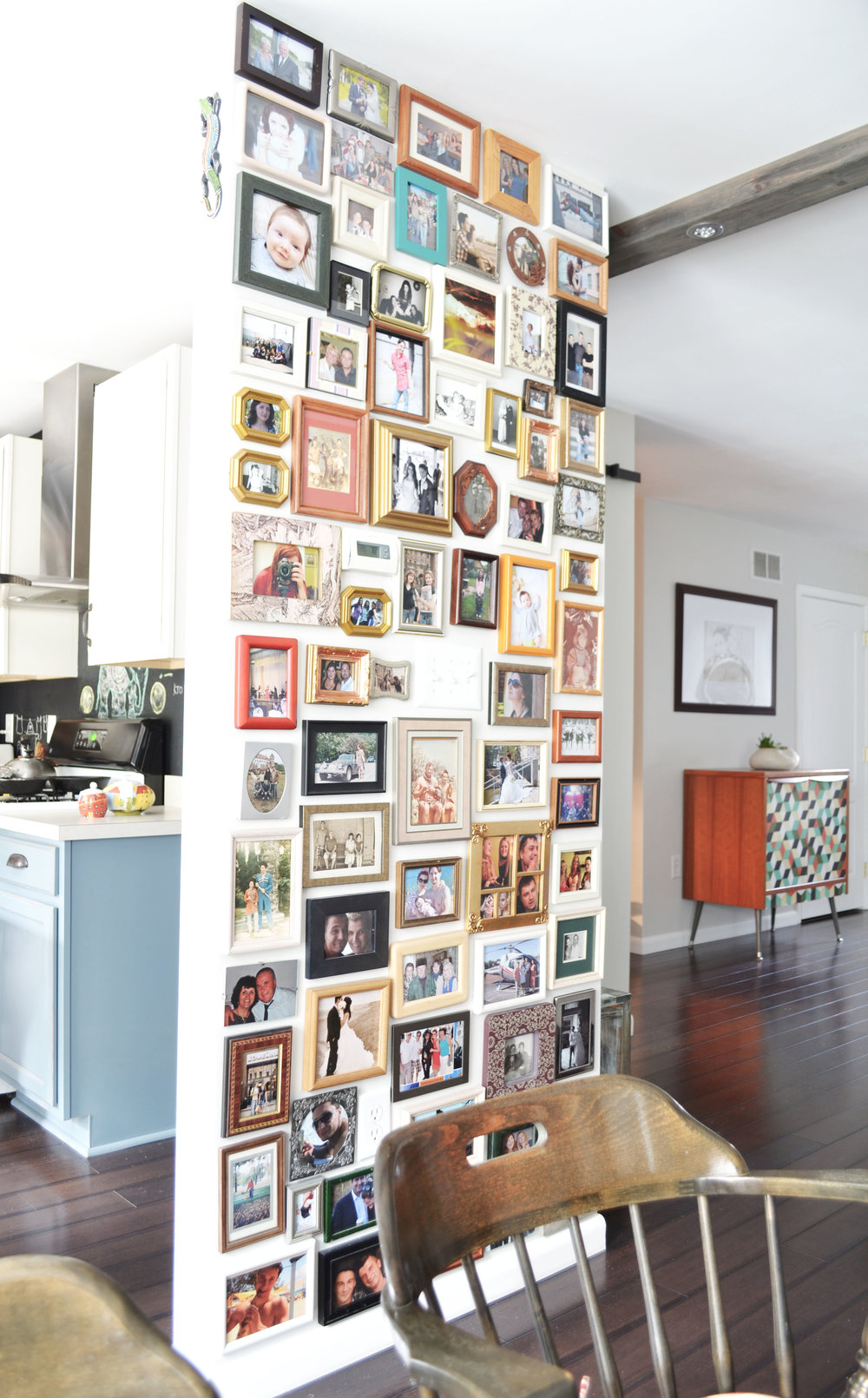 Floor to ceiling gallery wall with thrift store photo frames.