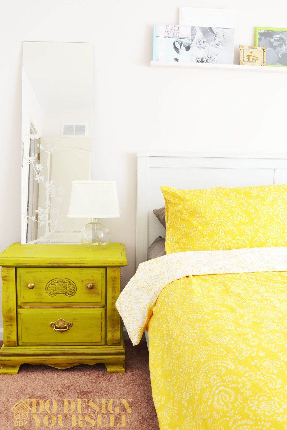 bright and airy guest bedroom decorated with the painted night stand, floating shelves and photo-albums.