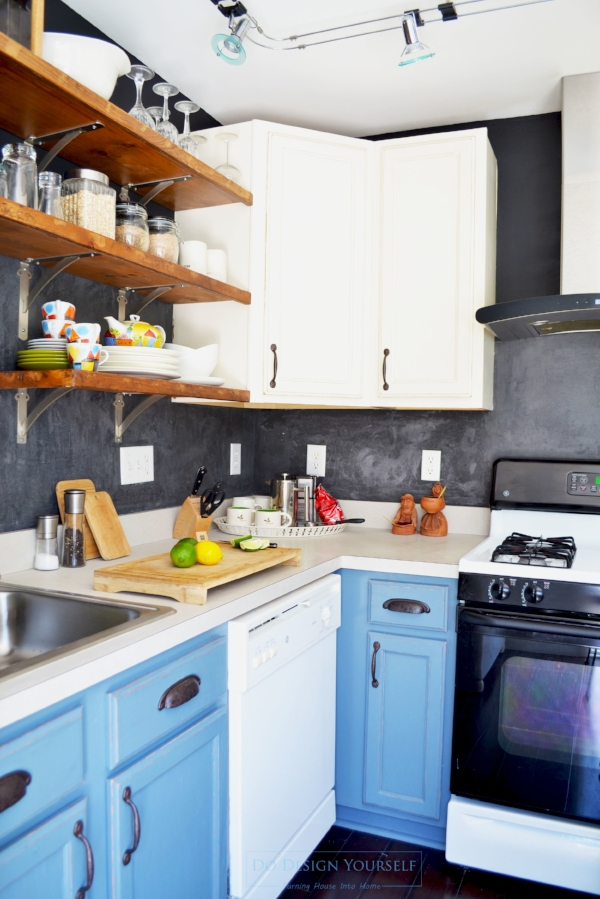 colorful blue and ivory painted kitchen cabinets. Black marmorino hydro distressed backsplash and industrial open shelves.