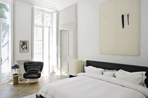 Minimalist bedroom with a large statement wall art. Source