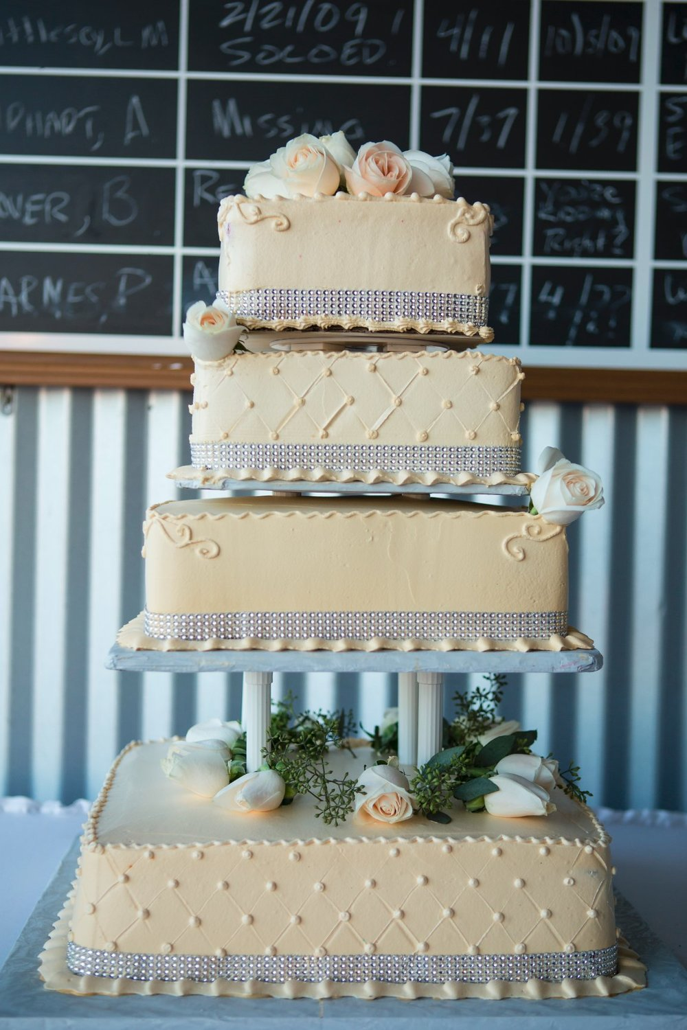 Classic tiered design with elegant ivory fondant and fresh roses. The sparkling crystal studded ribbon and tall columns gives this cake a regal feel. Cake by Ruby Carreon.