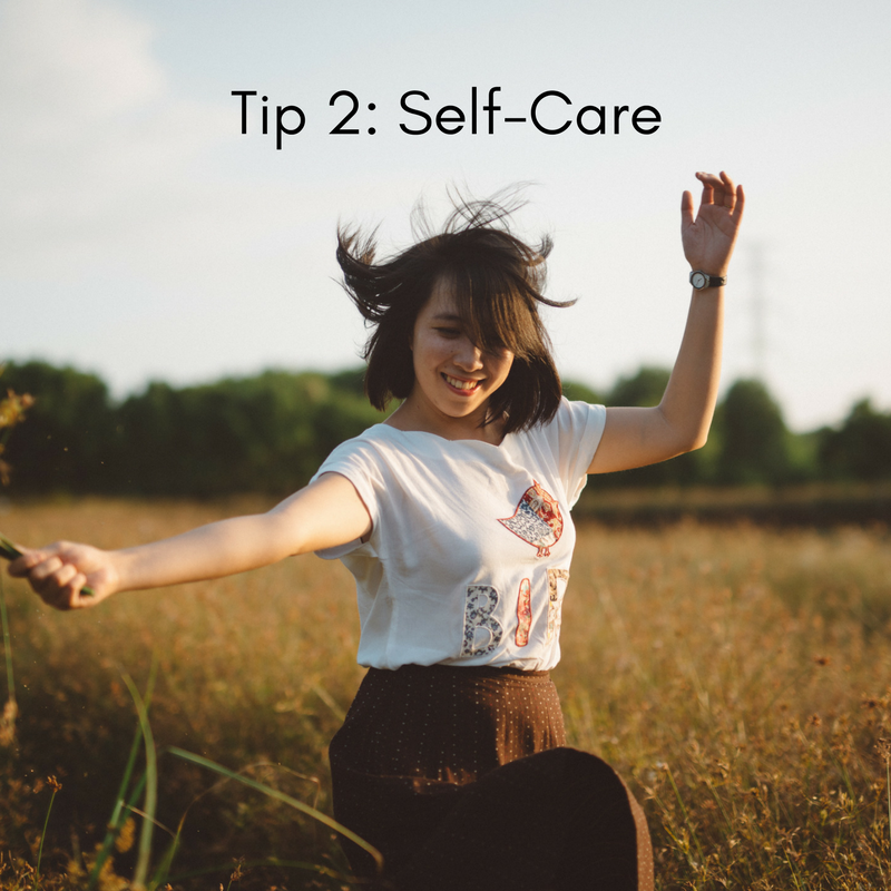 Image description: a woman dances in a field of grass with her arms outstretched. White text reads 'Tip 2: Self-Care'