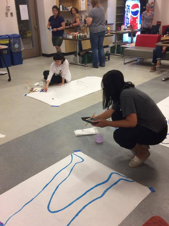 Participants started off by tracing their outlines in a variety of positions.  Image description: two people with large sheets of white paper trace their outlines in paint and crayon.