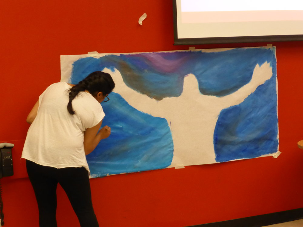 Participants engaged in a variety of creative forms, including using paints, oil and chalk pastels, marker, crayon, and other mediums to express themselves.  Image description: a participant paints a blue outline of their body on a large white sheet of paper against a red wall.